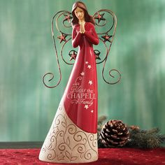 """A Personal Creations Exclusive! An inspirational holiday accent, our joyful angel bows her head in prayer. The stars on her red gown and gold wings are a beautiful reminder of the very first Christmas. We personalize her gown with any name, up to 12 characters. (""""Bless the"""" and """"Family"""" will always appear.) Crafted of resin and metal. Measures 10-1/2"""" H."""