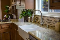 This farmhouse sink offers a classic look, while the two basins make it extra-functional for a hardworking kitchen. The mix of brown and tan tones in the mosaic tile backsplash tie together the colors of the warm wood cabinetry and cream-colored granite countertops.