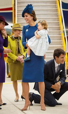 Kate held Charlotte in her arms as she chatted with welcoming dignitaries while, in the background, Prime Minister Justin Trudeau can be seen kneeling for some face-to-face time with Prince George. <br><br>Photo: © Pool/Getty Images