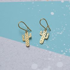 Etched brass or steel cactus earrings.   -Gold plated or solid silver ear wires.  -Designed & made in England by Dowse