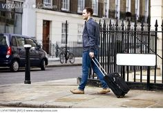 a_young_man_pulling_his_suitcase_in_the_street_LV14778056.jpg (650×453)