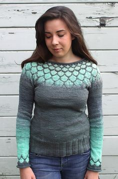 This mermaid inspired pullover sweater combines fair-isle patterning with the magic of ombré yarn. The bright mint fish-scale pattern on the yoke and sleeves blends slowly into a deep grey-green body. The sweater is knit from the top down in one piece, so there are no seams to sew and you can try it on and adjust the fit as you go.