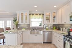White kitchen. stainless appliances. light stone floor. modern chrome drawer pulls