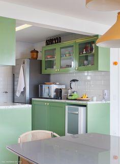 Cozinha integrada com piso de ladrilhos hidráulicos, armários verde pistache e paredes com subway tiles