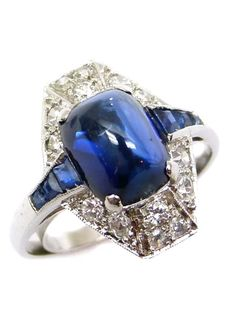 Art Deco cabochon sapphire and diamond cluster ring, French c.1920, the sugarloaf cabochon sapphire to a pave diamond shaped lozenge frame, tapered calibre cut sapphire shoulders, mounted in platinum