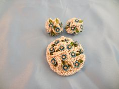 White delicately beaded brooch with Blue flower detail.  In person this brooch is bright white.