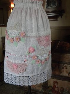 "Embriodered batiste embelished with beautiful pink crocheted doilies, crocheted roses,pearls,satin flowers, ribbons and lace trims too numerous to mention cover this shabby chic delight.The apron has a elastic comfort waistband. Beautiful double ribbon ties. apron is 27"" long including 4"" lace trim on the bottom. thank you for visiting my shop Grace"