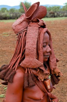 "Himba woman wearing "" leopard cone "" shell (conus leopardus)  , and elaborate Himba headwear. Namibia / Angola border 