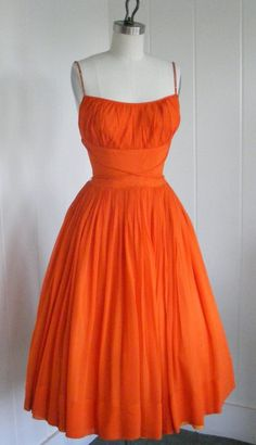 A fabulous 1950's tangerine chiffon cocktail party dress with rhinestone straps, tulle underskirt, taffeta lining, ruched bust, nipped waist and full circular skirt.
