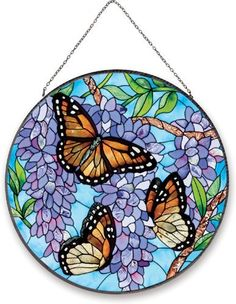 "Joan Baker Designs AP402 Wings and Wisteria Glass Art Panel, 10-Inch Diameter by Joan Baker Designs. $36.99. Timeless best-seller. Bronzed metal frame with chain. Romantic as an english garden. Hand-painted art glass window panel. Ap402 10""diam. Cascading purple wisteria attracts 3 stunning monarch butterflies in this dramatic Art Panel. Rich colors and intricate detail make this hand-painted art glass piece a perfect gift or element of home décor for your window. for more th..."