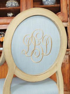 Soft blue fabric is paired with white distressed wood for a traditional dining room chair. A script monogram adds an elegant touch to the oval backed chair.