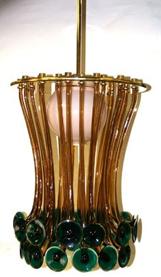 """Ettore Sottsass \""""Formossa\"""" Murano art glass Chandelier for Venini.  28 Amber rods with everted green disc at ends.  with Internal globe shade.  Approx. 34\"""" from ceiling.  Extreme arm length; 20 1/4\"""".  16\"""" dia.  Excellent condition."""