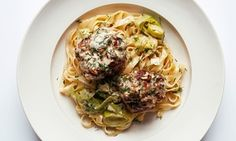 Sausage meatballs on top of a pile of leek tagliatelle on a plate