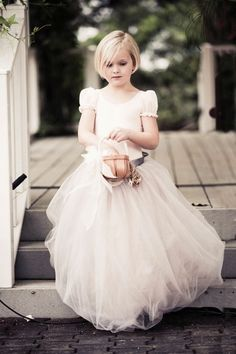 The flower girl walks down the aisle in a dress made by the bride.