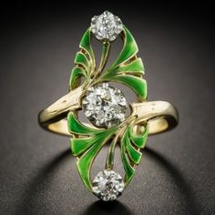 Measuring an impressive 1 inch long, this distinctive, striking, and utterly enchanting original Art Nouveau dinner ring, artfully hand fabricated in platinum and 18K gold, circa 1900, presents a trio of bright white and sparkling European-cut diamonds blossoming among bright green enameled fronds. One-of-a-kind. Currently ring size 5 1/4.
