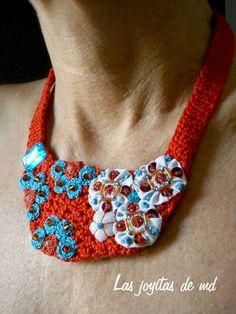 Sobre una base de croché en color rojo he cosido yoyos de tela, rosetas en color rojo y turquesa, lentejuelas y cristal de swarovski.