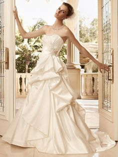 This silky style offers the peplum feature to show off your waist on your glorious wedding day…it is Casablanca Bridal 2111 wedding dress and it is very special. With a strapless neckline that is glamorously ruched and midriff adorn with an applique of Swarovski crystals, rhinestones and pearls, you begin to realize why all the smiles are so big and why your groom is waiting impatiently at the altar.
