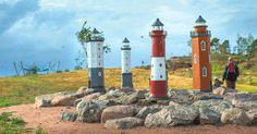 Seitsemän pienoismallia Suomenlahden majakoista hohtavat valoa pimeään Katariinan Meripuistossa. Taustalla näkyvät riippumatot, joista on näköala merelle.