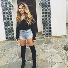 Who says you can't wear tall boots with your Daisy Dukes? Jessie James proves you definitely can with this black long sleeve top, western-style belt, and light-washed shorts.