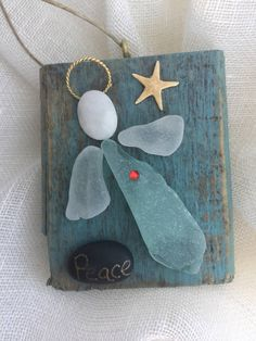Piece of driftwood painted with as chalk paint then distressed then sealed. The angel is genuine sea glass. Her head is a cape My pebble and she has a swarovski chrystal heart.Also a genuine starfish looking over her.