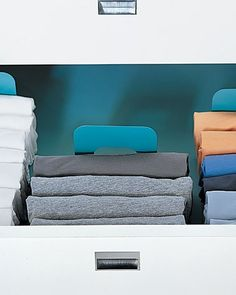 This End Up  Tame your T-shirts by folding them into thirds and arranging them folded-end up in the drawer, rather than flat (this is an overhead view). Metal bookends, painted blue and outfitted with rubber surface protectors, hold the shirts upright, letting you see each one.