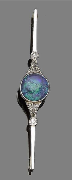 An early 20th century black opal and diamond bar brooch, circa 1915  Centrally-set with a circular cabochon black opal, between old brilliant and rose-cut diamonds, length 6.6cm