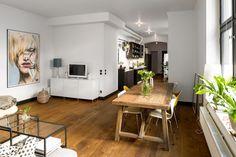 drewniana podłoga,drewniany stół prostokatny z nowoczesnymi krzesłami,nowoczesny obraz i białe szafki w otwartym salonie z kuchnią i jadalnią - Lovingit.pl