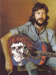 Eric Clapton with a Grateful Dead skull and roses guitar.