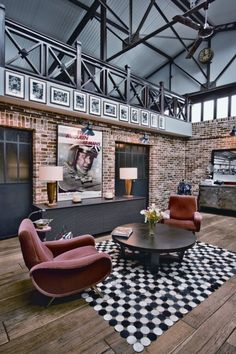Exposed steel vaulted ceiling, black ceiling fan, natural floorboards, exposed brick, black balustrades for upper mezzanine