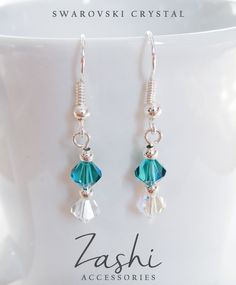 Add sophisticated sparkle to your look with these prismatic real Swarovski crystal earrings. You are sure to love the bedazzling crystal bicone beads that are accented with tiny silver beads. The Swarovski Indicolte color gives off a turquoise hue in daylight and a deep blueish-green in the dark. The clear Crystal AB finish on the bottom bead gives off a mesmerizing spectrum of colors.
