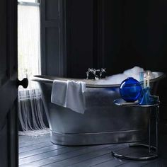 Gothic bathroom  A silver-leaf bath gleams in this dark and romantic bathroom. A chain mail waterfall is a modern alternative to a curtain or blind and brings a touch of fantasy to the room. Blue candles and glass vases add colourful accents.