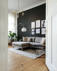 Living room with high ceilings and dark grey wall in a Lovely, Understated, Warm. Living room with high ceilings and dark grey wall in a Lovely, Understated, Warm and Inviting Berlin Home Dark Walls Living Room, Feature Wall Living Room, Rugs In Living Room, Home And Living, Living Room Decor, Tiny Living, Modern Living, Dark Grey Rooms, Modern Wall