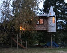Awesome looking tree house with a turret & circular staircase.