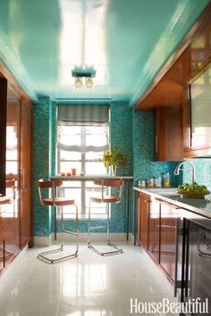 In the kitchen of a Manhattan apartment by Philip Gorrivan, iridescent mosaic tiles and a ceiling lacquered in Benjamin Moore's Oceanic Teal pick up a color from the wallpaper in the hallway. The Thonet barstools are by York Street Studio.