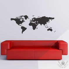 Black world map wall decal as a silhouette placed on a white wall above a red modern couch.