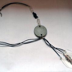 """Sautoir """"L'original"""" - collection """"Black & White"""" (par Sésé'Dille).    Vous ne passerez pas inaperçu avec ce collier sautoir pour le moins original tout en associant la sophistication du noir et blanc !    Ce collier est composé d'un pendentif en béton rond, de pampilles de pierres de quartz cristal et noir, de plumes blanches, d'une breloque en métal argenté en forme de plume et d'un double cordon en cuir noir de 3 mm."""