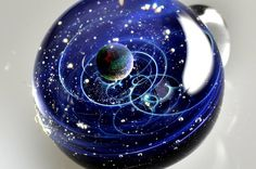 Glass artist Satoshi Tomizu sculpts small glass spheres that appear to contain entire solar systems and galaxies.