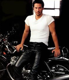 Actor Keanu Reeves dressed in black leather pants and his motorcycle