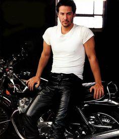 Actor Keanu Reeves dressed in black leather pants and his motorcycle