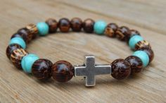 About the Bracelet An inspirational and spiritual mens beaded cross bracelet. A nice casual look and feel. Bracelet Details: This mens bracelet is made with: - 8/9mm Palm Wood - 8mm Howlite - Cross Be