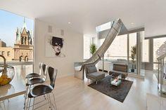 maison avec toboggan métallique, salon design avec faux plafond, fauteuils gris et tapis assorti