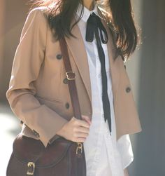 Very cute brown coat with a white shirt and black ribbon around the neck. Along with the maroon colored purse.