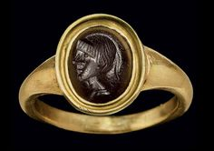 A ROMAN BLACK JASPER RINGSTONE CIRCA 1ST CENTURY B.C. The convex oval stone engraved with the bust of a youth in profile to the left; mounted as a ring in a modern gold setting | Christie's