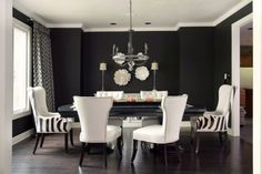 Black and white dining room with striped armchairs.