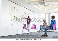 Businesswoman giving presentation to colleagues in creative office space - stock photo