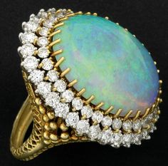 LARGE OPAL AND DIAMOND RING Platinum and 18k yellow gold with a very fine oval cabochon blue/green opal, approx. 18.7 cts., surrounded by two rows of circular brilliant cut diamonds, approx. 6 cts.  mid-20th century. Elaborate hand-built setting. Unsigned, numbered 1696. 19.5 gms.