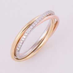 Three Tone trinity ring in 14k or 18k rose, yellow and white gold set with clear diamonds. The ring is made from 3 bands. The bands are soldered and they do not roll so the white gold diamond band (half eternity style) is always on top. There is also an option to make this ring as a rolling