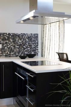 A modern black kitchen with white countertops, a sleek stainless steel hood, and a mosaic tile backsplash. (Kitchen #5)