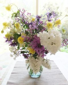 A beautiful bouquet of english country garden spring flowers - white lilac, hesperis, daffodils, aquilegia and perennial cornflower