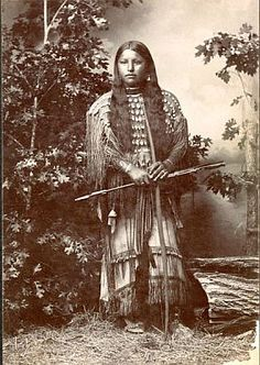 A Kiowa woman wearing a traditional dress decorated with beadwork, a necklace of bone beads and hair ornaments of rabbit fur and beadwork. Description from pinterest.com. I searched for this on bing.com/images